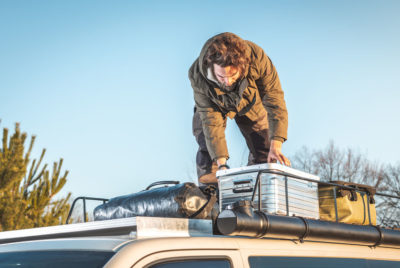 Man Standing On Top Of His Bug Out Vehicle Roof Rack